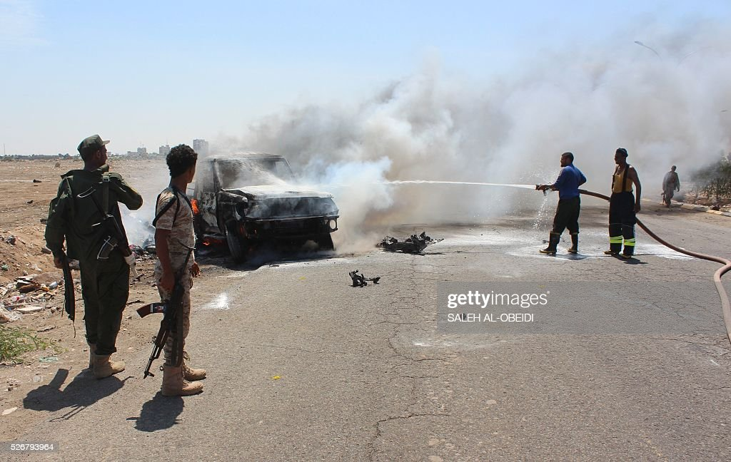 Yemeni security forces extinguish fire at a site where a bomb-laden car exploded in Aden's Mansura district on May 1, 2016. A bomb-laden car exploded as General Shallal Shayae's convoy passed, damaging military vehicles and prompting clashes between his guards and Al-Qaeda suspects in the area, officials said, adding that four Yemeni guards were killed in the bombing that targeted the convoy of Aden's police chief, the second such attack on him this week. / AFP / SALEH