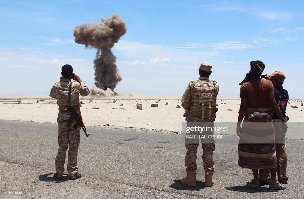 Yemeni security forces look at smoke billowing from the desert of al-Alam, east of the southern port city of Aden, on April 29, 2016, during a controlled explosion to destroy explosives and mines laid by Al-Qaeda militants in the Lahj province. / AFP / SALEH