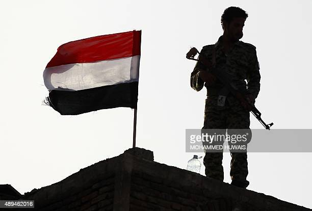 A Yemeni Shiite Huthi rebel stands next to a national flag in the capital Sanaa on September 21 during a ceremony marking a year since the city's...
