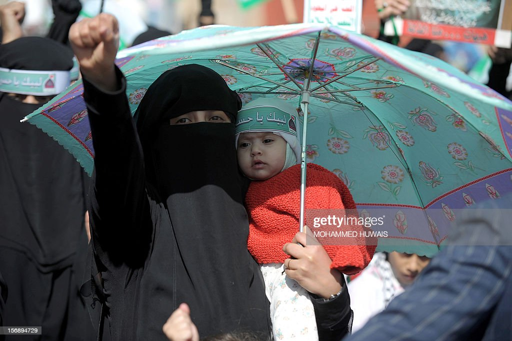 A Yemeni Shiite woman holding a baby raises her fist as she takes part in a march during Ashura celebrations in Sanaa on November 24, 2012.