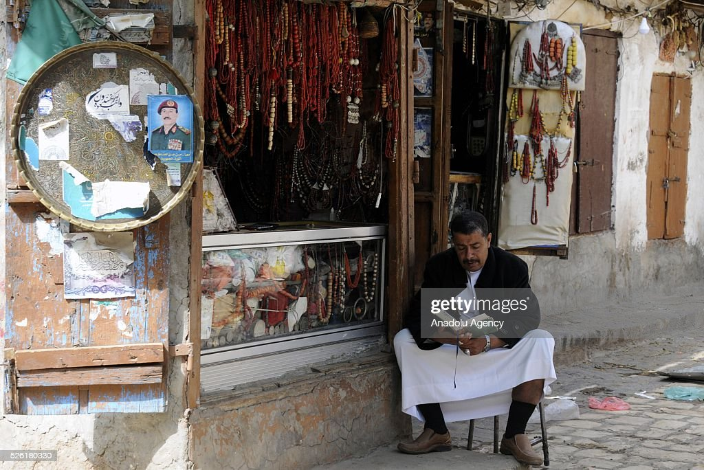 A Yemeni shopkeeper man reads a book as the peace talks organized in Kuwait continues in Sanaa, Yemen on April 29, 2016.