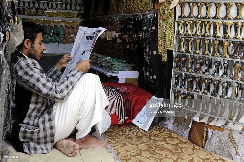 A Yemeni shopkeeper man reads a newspaper as the peace talks organized in Kuwait continues in Sanaa, Yemen on April 29, 2016.