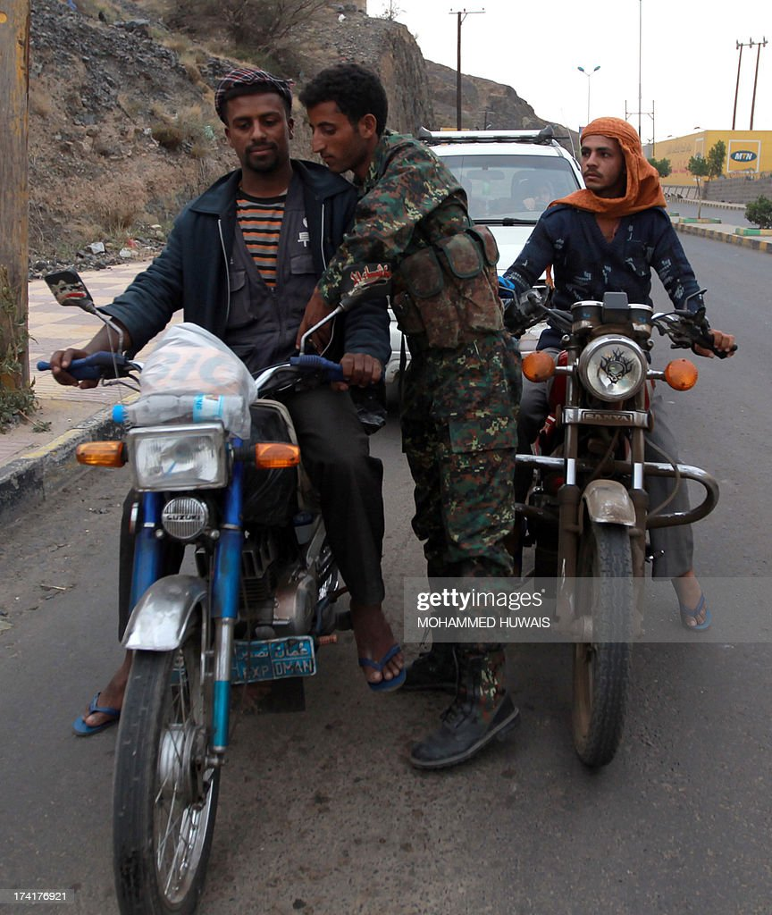 A Yemeni soldier searches a motorcycle at a checkpoint in Sanaa, on July 21, 2013, as authorities tighten security measures after gunmen suspected of being members of Al-Qaeda kidnapped an Iranian diplomat in broad daylight in the Yemeni capital, according to police. AFP PHOTO/ MOHAMMED HUWAIS