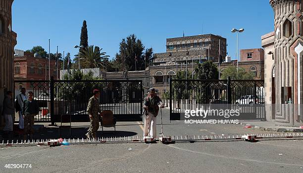 Yemeni soldiers and Houthi militiamen stand guard at the entrance of the Presidential Palace following a blast in Sanaa on February 7 2015 Yemen...