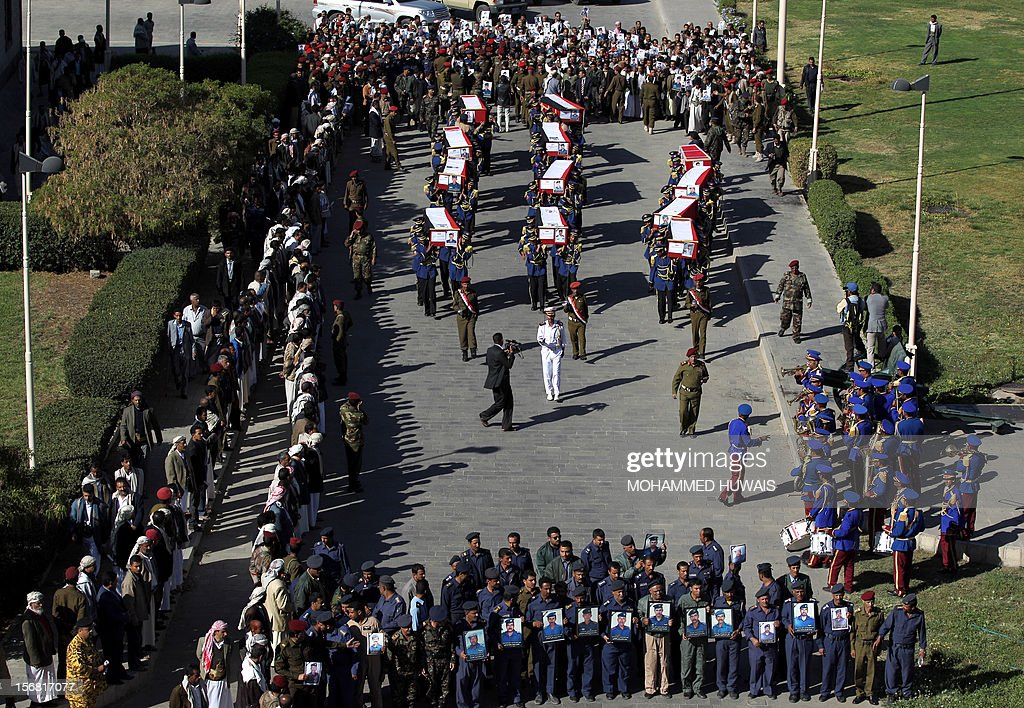 Yemeni soldiers carry the coffins of ten comrads killed in a crash of a military plane the previous day, during a funeral service in Sanaa on November 22, 2012. The plane crashed on November 20 as it tried to make an emergency landing when an engine failed, accorading Yemen's defence ministry. AFP PHOTO/MOHAMMED HUWAIS