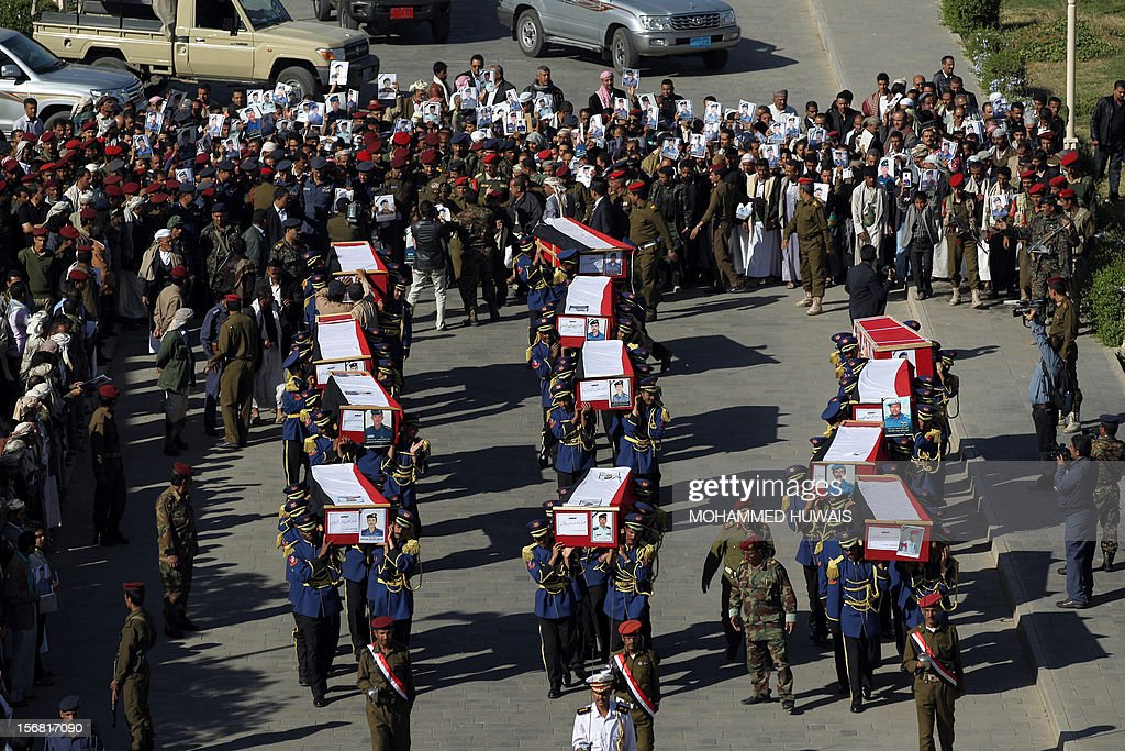 Yemeni soldiers carry the coffins of ten comrads killed in a crash of a military plane the previous day, during a funeral service in Sanaa on November 22, 2012. The plane crashed on November 20 as it tried to make an emergency landing when an engine failed, accorading Yemen's defence ministry.