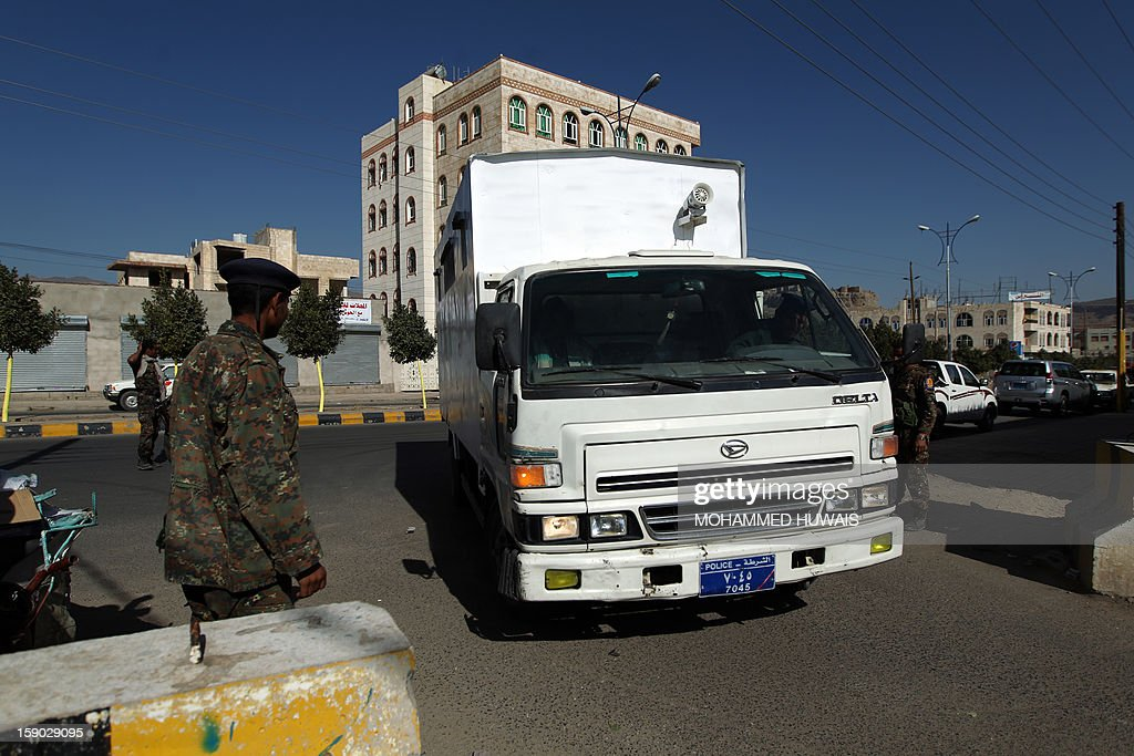 Yemeni soldiers stand guard outside the state security court as suspected Yemeni al-Qaeda militants arrive in a truck for their trial on January 6, 2013 in the Yemeni capital Sanaa.