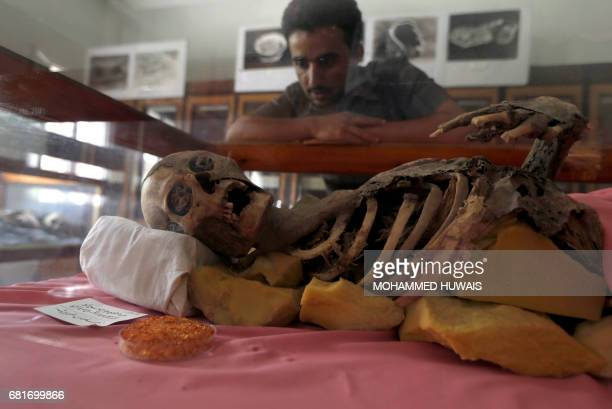 A Yemeni student looks at a milleniaold mummy displayed at Sanaa University in the Yemeni capital on May 10 2017 Yemen's war has claimed thousands of...