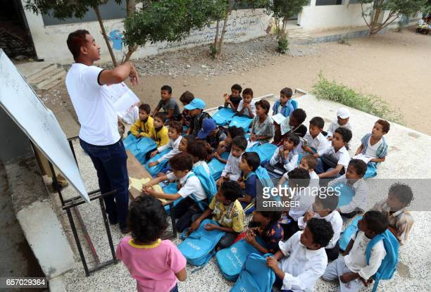 Yemeni students attend a class outside in the Yemeni port city of Hodeidah on March 15 after their school was damaged in the country's ongoing...