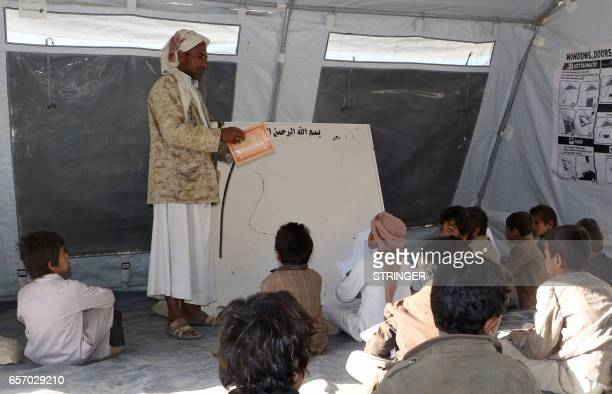 Yemeni students study in a tent serving as classroom at a school was damaged in the country's ongoing conflict between the Saudiled Arab coalition...