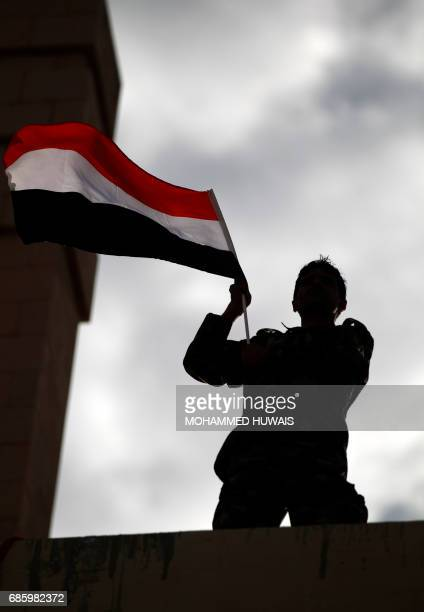 A Yemeni supporter of the Huthi rebels waves a national flag during an antiUS protest in Sanaa on May 20 2017 US President Donald Trump began an...
