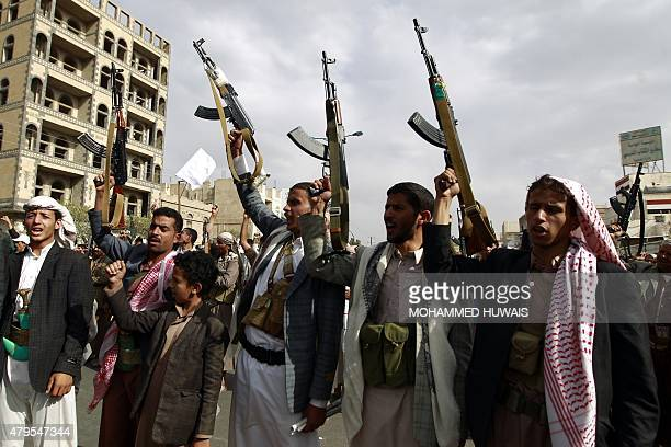 Yemeni supporters of the Shiite Huthi movement raise their weapons during a rally in the capital Sanaa on July 5 protesting against air strikes by...