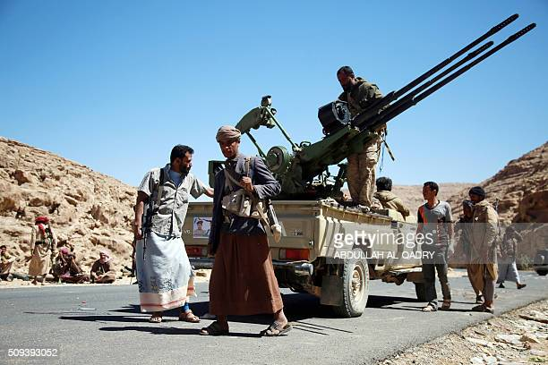 Yemeni tribesmen from the Popular Resistance Committees supporting forces loyal to Yemen's Saudibacked President stand next to a vehicle as they...