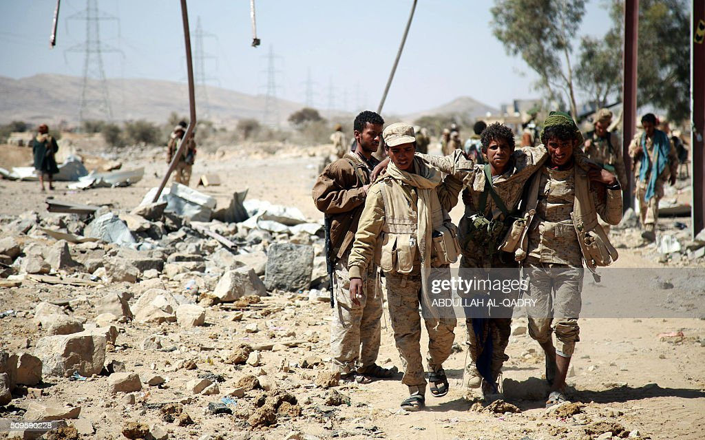 Yemeni tribesmen from the Popular Resistance Committees, supporting forces loyal to Yemen's Saudi-backed President, help an injured comrade in the Nehm camp in the Nehm region, west of Marib city, as the fight against Shiite Huthi rebels and their allies continues, on February 11, 2016. / AFP / ABDULLAH AL-QADRY