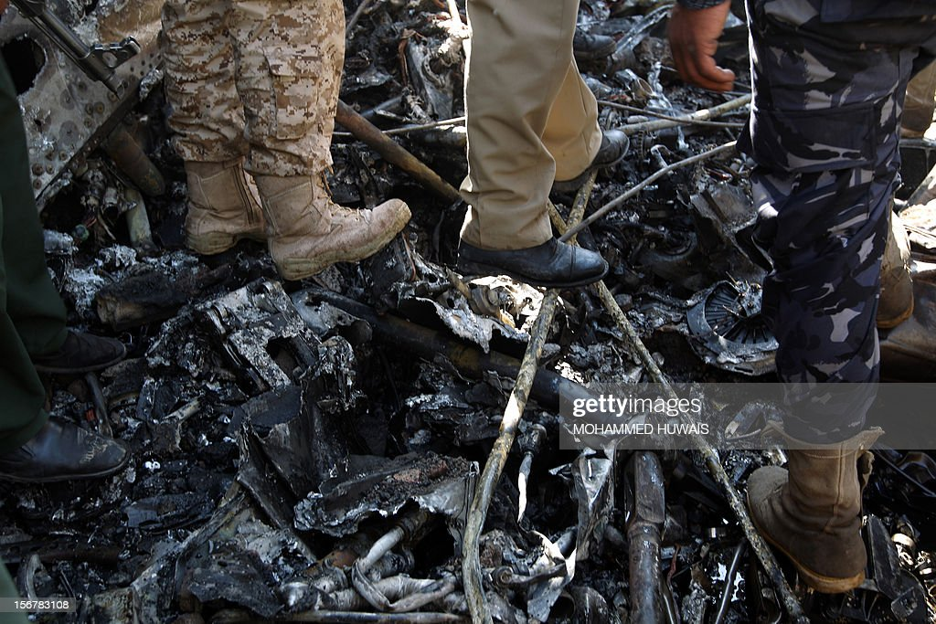 Yemeni troops inspect the scene where a military plane crashed in Sanaa on November 21, 2012, killing 10 people including the pilot, as it tried to make an emergency landing when an engine failed, according to Yemen's defence ministry and an airport source. The Antonov plane crashed in the Yemeni capital's northern neighbourhood of al-Hassaba while trying to land at an air base near Sanaa's main airport. AFP PHOTO/ MOHAMMED HUWAIS