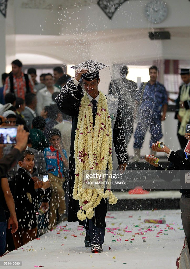 A Yemeni University graduate is sprayed with confetti during a graduation ceremony in the Yemeni capital Sanaa on May 26, 2016. / AFP / MOHAMMED
