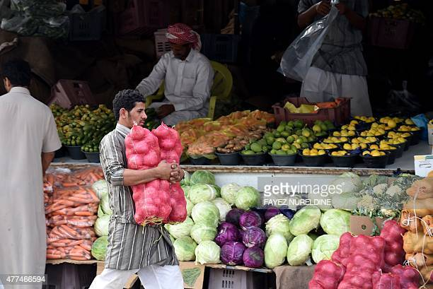 A Yemeni vendor living in Saudi Arabia carries bags of onions at Otaiga public market in the Manfouha district of the capital Riyadh on June 17 2015...