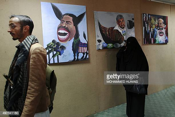 Yemeni visitors one of them carrying a traditional dagger look at paintings displayed during an exhibition denouncing the support provided by Yemeni...