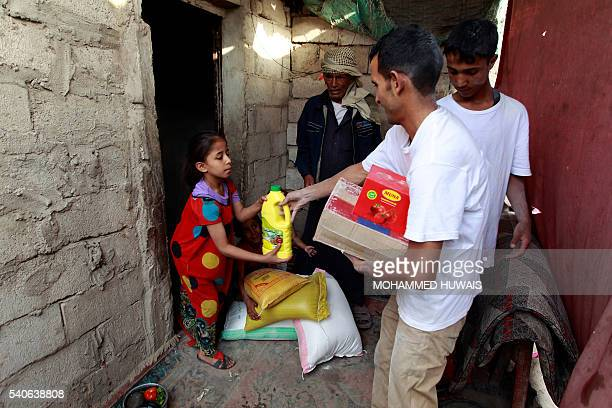 Yemeni volunteers of a local charity distribute food rations to families affected by the country's ongoing conflict on June 15 2016 during the...