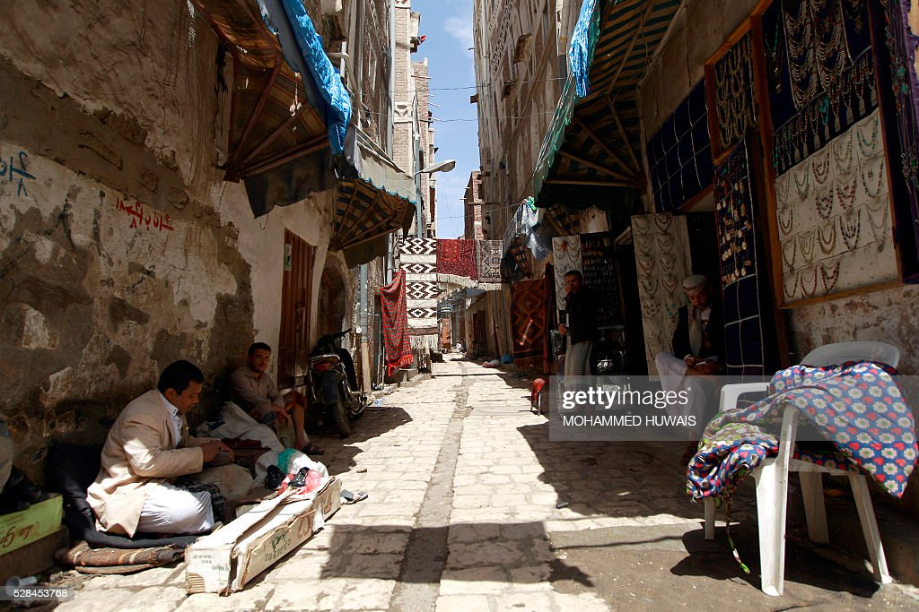 Yemeni wait outside their shops in the old city of the capital Sanaa on May 5, 2016. / AFP / MOHAMMED