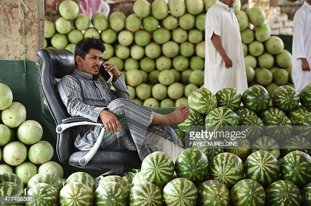 A Yemeni watermelons vendor living in Saudi Arabia talks on the phone as he is waiting for customers at Otaiga public market in the Manfouha district...