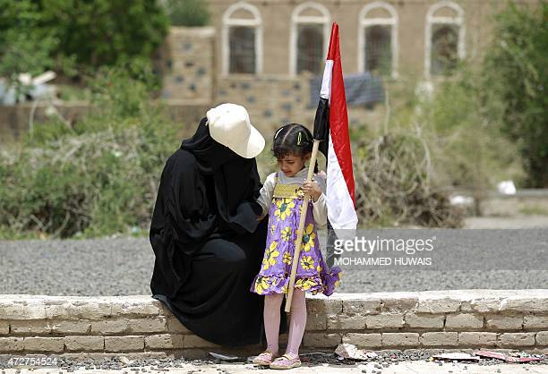 A Yemeni woman and child holding her national flag rest on wall during a rally protesting against the Saudiled airstrikes targeting Shiite Huthi...