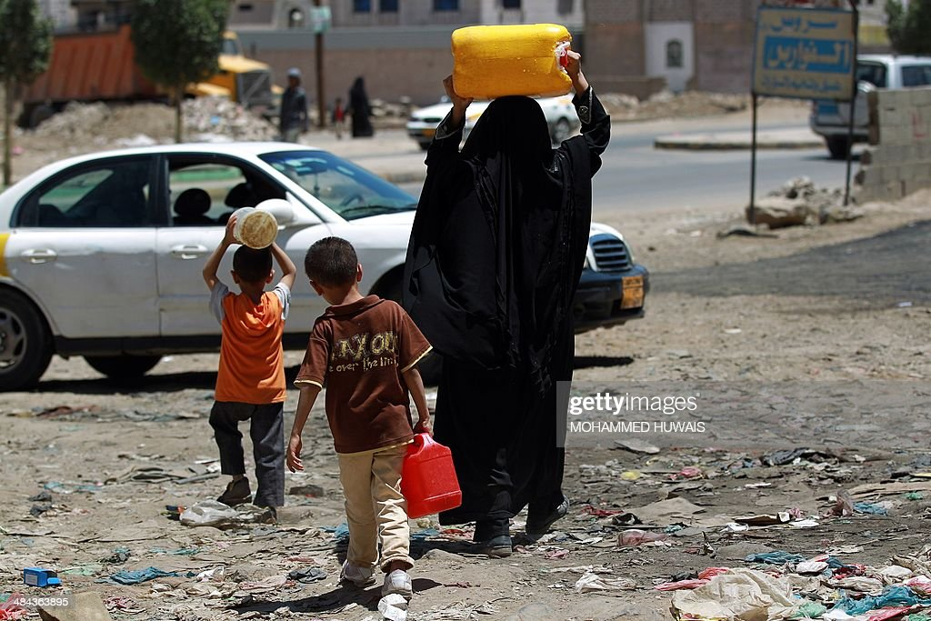 A Yemeni woman and her children, carry jerry cans as they leave after filling them at a public tap on April 12, 2014 at a slum in the capital Sanaa. Yemen, ravaged by years of factional strife and widespread poverty, is one of the world's most water-stressed countries with the lack of access to clean water having devastating implications for children.