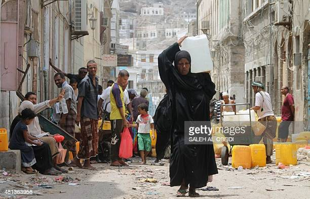 A Yemeni woman carries a plastic container filled with water in the southern Red Sea port city of Aden on July 19 2015 Backed by air support from...