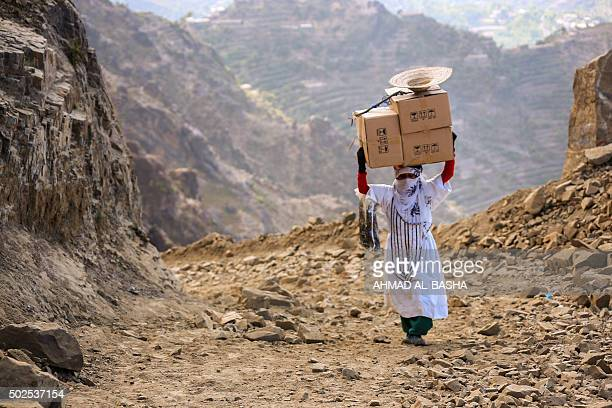 Yemeni woman carries boxes of food on her head as she walks through the mountains along the only path accessible between the southern cities of Aden...