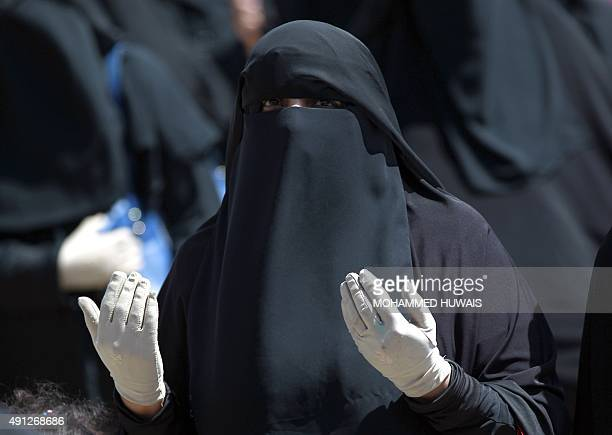 A Yemeni woman dressed in the niqab prays as she takes part in a demonstration on October 4 2015 in front of the United Nations office in the Yemeni...