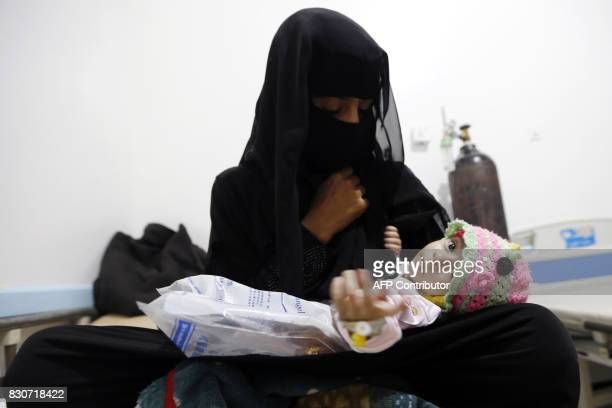A Yemeni woman holds her child who is suspected of being infected with cholera at a makeshift hospital in the capital Sanaa on August 12 2017 A...