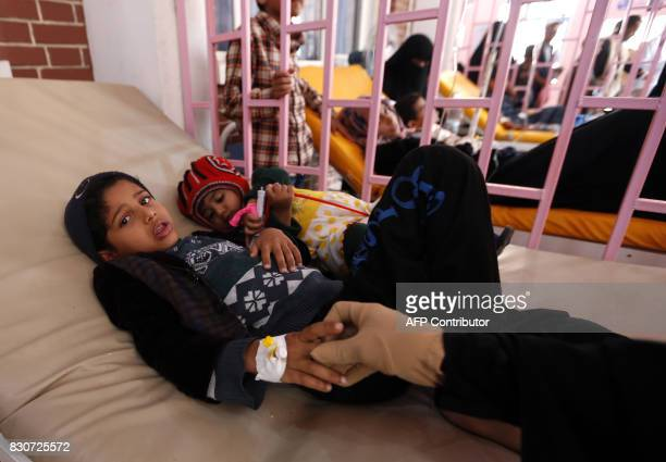 A Yemeni woman holds the hand of one of her children who is suspected of being infected with cholera as they receive treatment at a hospital in the...