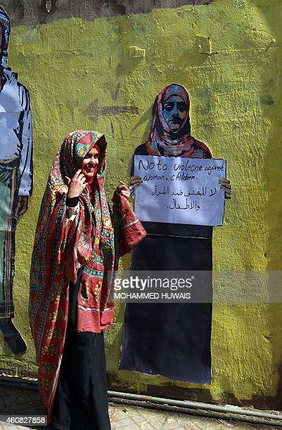 A Yemeni woman in traditional dress stands in front of graffiti bearing an antiviolence message on a wall in the capital Sanaa on December 25 2014...