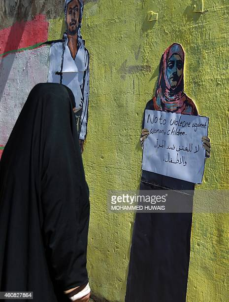 A Yemeni woman looks at graffiti bearing an antiviolence message on a wall in the capital Sanaa on December 25 2014 AFP PHOTO / MOHAMMED HUWAIS