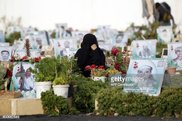 A Yemeni woman sits next to the grave of a loved one in a cemetery in the capital Sana on June 25 2017 after the Eid alFitr prayer which marks the...