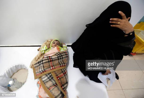 A Yemeni woman sits with a child as patients suspected of being infected with cholera receive treatment at a hospital in Sanaa on May 6 2017 At least...