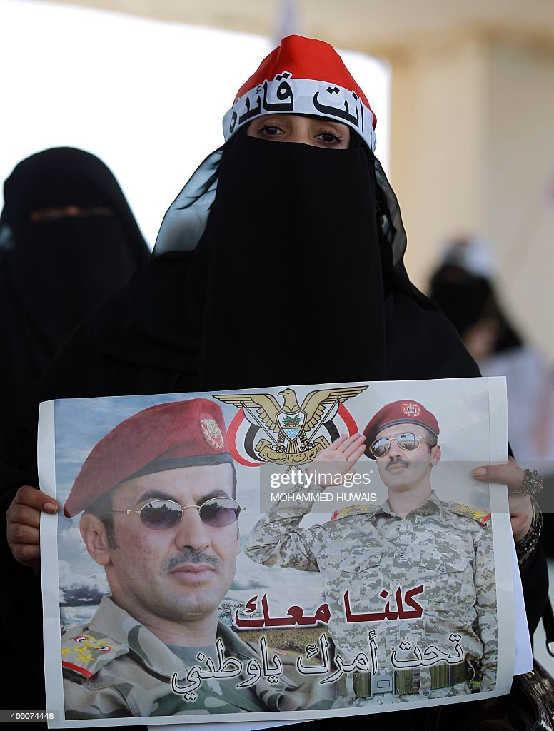 A Yemeni woman takes part in a demonstration outside the house of Ahmed Ali Abdullah Saleh (portrait), the son of Yemen's former president Ali Abdullah Saleh who stepped down in early 2012, calling for presidential elections and demanding the son of the ex-strongman to run as a candidate, on March 13, 2015 in Sanaa. The poster reads in Arabic: 'We are all with you under your command, my nation'. AFP PHOTO / MOHAMMED HUWAIS