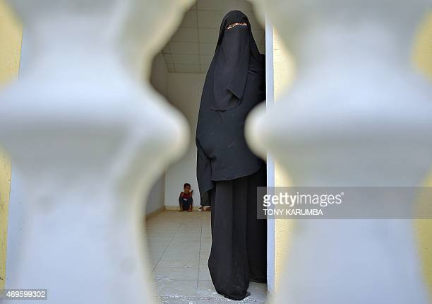 A Yemeni woman waits by the door for the rest of her family at a designated quarters along with other newly arrived refugees on April 13 2015 at a...