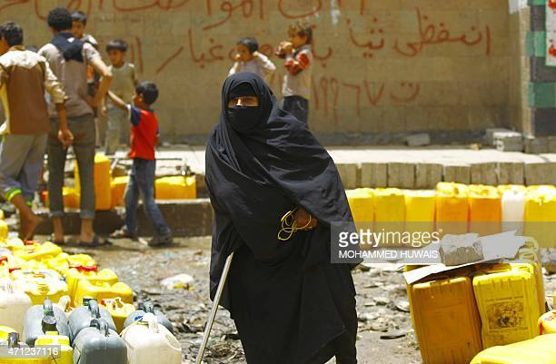 A Yemeni woman waits to fill her jerrycans with water from a public tap amid an acute shortage of water supply to houses in the capital Sanaa on...