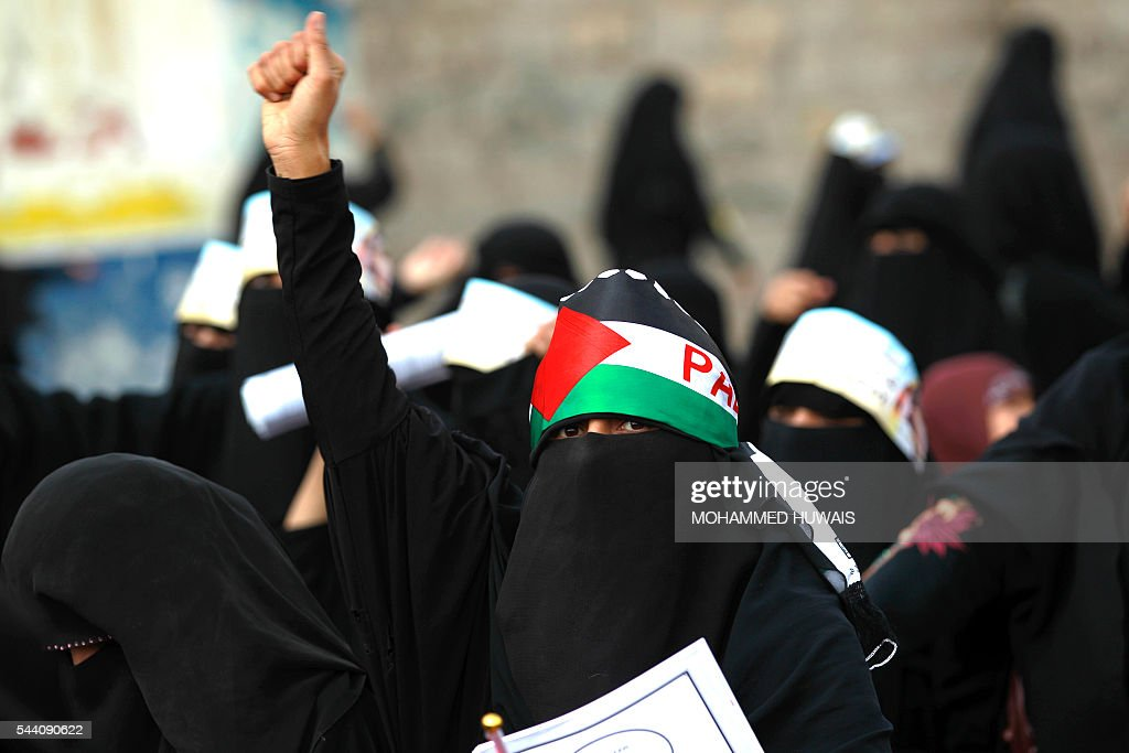 A Yemeni woman wears a Palestinian flag as a headband during a rally gathering supporters of the Shiite Huthi movementto mark the Quds (Jerusalem) International day, in support of Palestinians on July 1, 2016 in the capital Sanaa. / AFP / MOHAMMED