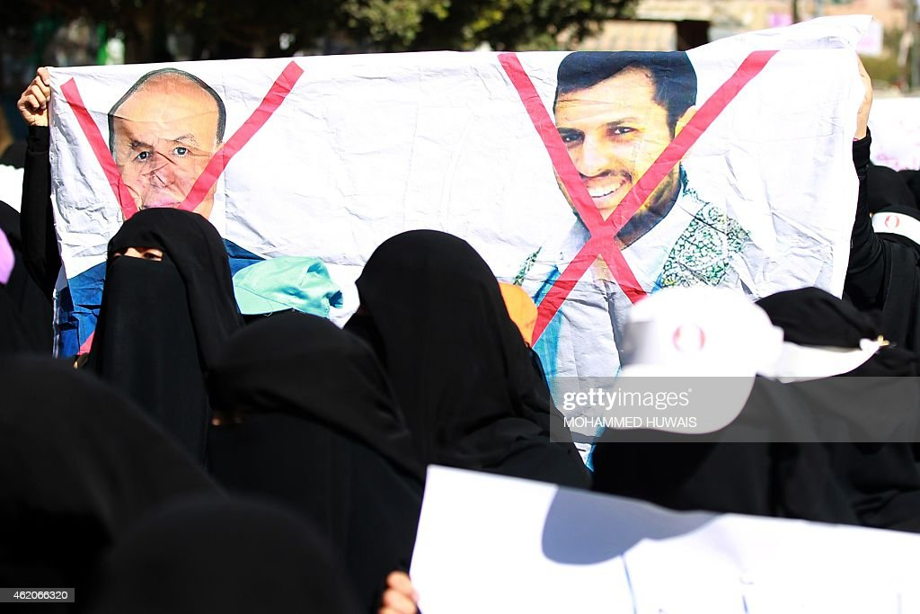 Yemeni women hold a banner bearing red crosses on portraits of Yemeni former president Abdrabuh Mansur Hadi and Shiite Huthi movement's leader Abdul-Malik al-Huthi (R) during a rally against the control of the capital by Huthi rebels on January 24, 2015 in the capital Sanaa. Thousands of Yemenis took to the streets of Sanaa in the largest demonstration against Huthis since the Shiite militiamen overran the capital in September. 'Down, down with the Huthis' rule,' chanted the protesters who rallied following a call by the Rejection Movement -- a group recently formed in provincial areas to challenge the powerful militia. AFP PHOTO / MOHAMMED HUWAIS