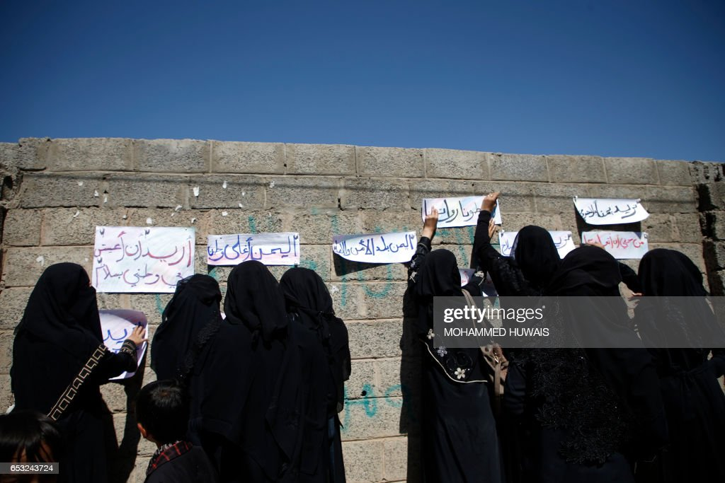 Yemeni women put up slogans in Arabic calling for peace during a sit-in on March 14, 2017 outside the United Nations (UN) offices in the capital, Sanaa, demanding an end to a war that has left millions displaced and at risk of famine. / AFP PHOTO / Mohammed HUWAIS