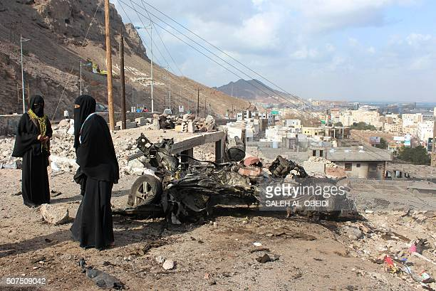 Yemeni women stand next to the remains of a vehicle at the site of bombing that targeted a police checkpoint the night before in the country's second...