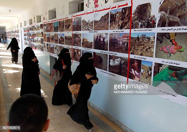 Yemeni women walk past a banner depicting images of hospitals and health centers allegedly destroyed by Saudiled airstrikes during an antiwar gallery...