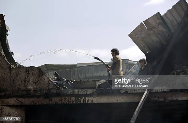 A Yemeni worker pours water on a chocolate factory on September 17 2015 which was destroyed by air strikes carried out by the Saudiled coalition in...
