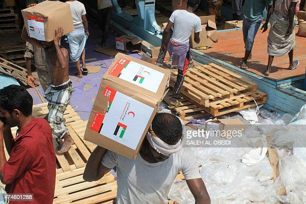 Yemeni workers unload medical aid boxes from a boat carrying 460 tonnes of Emirati relief aid that docked in the port of the city of Aden on May 24...