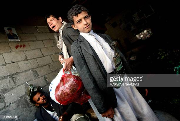 A Yemeni youth wearing the traditional dagger stands at the entrance of a shop that sells qat a mild drug used daily by most Yemenis at a market in...