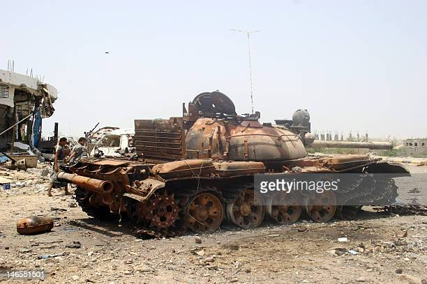 Yemeni youths walk past a destroyed tank in the the restive southern city of Zinjibar on June 19 2012 as Yemeni forces continue their offensive...