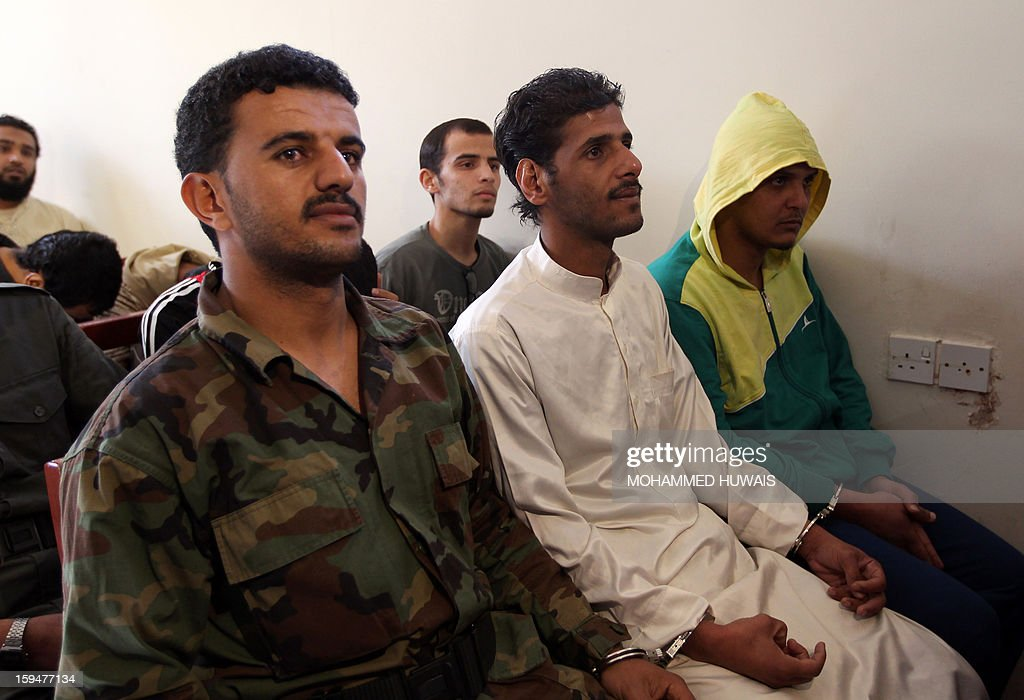 Yemenis allegedly accused of complicity in a suicide bombing that had killed 86 soldiers in May 2012, attend their trial at a state security court in Sanaa on January 14, 2013. The nine defendants who belong to an Al-Qaeda terrorist cell called Sawane, have notably been accused of 'participation in armed gang, conspiracy to assassinate officials.' AFP PHOTO/ MOHAMMED HUWAIS