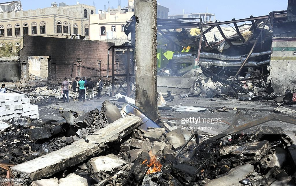 Yemenis are seen near the wreckage of collapsed building after Saudi-led coalition airstrikes hit a bowling saloon at Musbahi district in Sanaa, Yemen on February 12, 2016.